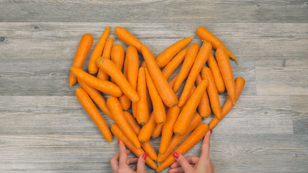 Closeup of womans and childs hands put carrots in the shape of a heart on a white background in fast motion. Healthy food concept
