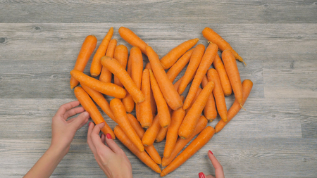Closeup of womans hands put carrots in the shape of a heart on a white background. Healthy food concept