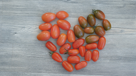 Closeup of different color cherry tomatoes in the shape of a heart on a wooden background. Healthy food concept