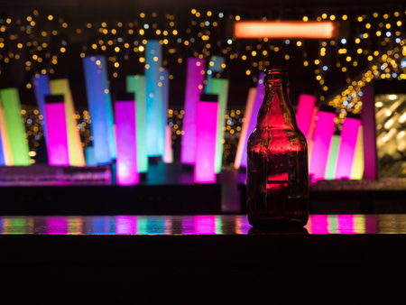 Dark glass beer bottle at the bar counter with colour changing decoration glowing flashing lamp cylinder column fluorescent neon on background Stock Photo