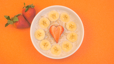 ceramic bowl with oatmeal porridge with bananas and strawberry