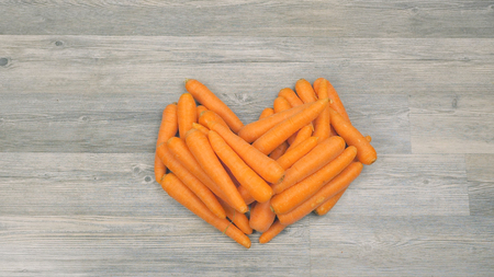 Closeup of carrots puted in the shape of a heart on a wooden background. Healthy food concept