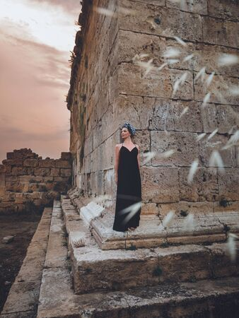 Close-up view of beautiful young, attractive Muslim woman in long black dress and headscarf standing on the corner of Hidirlik tower old Roman Empire tower in Antalya, Turkey Stock Photo - 132051148