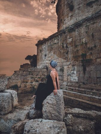 Beautiful middle-aged woman in long black dress and headscarf sitting on the stone in front of Hidirlik tower old Roman Empire tower in Antalya, Turkey Stock fotó