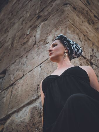 Beautiful young, attractive Muslim woman in long black dress and headscarf standing on the corner of Hidirlik tower old Roman Empire tower in Antalya, Turkey Stock Photo - 132051099