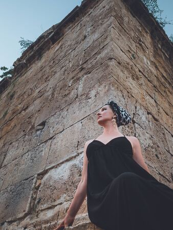 Close-up view of beautiful young, attractive Muslim woman in long black dress and headscarf standing on the corner of Hidirlik tower old Roman Empire tower in Antalya, Turkey