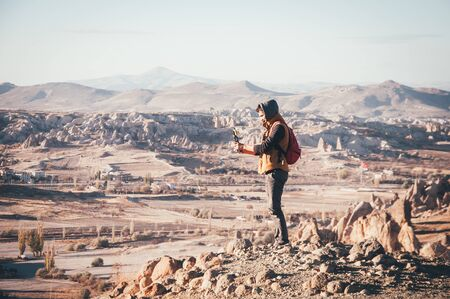 Man traveler taking photos with gorilla pod of beautiful panoramic view in Cappadocia in autumn time