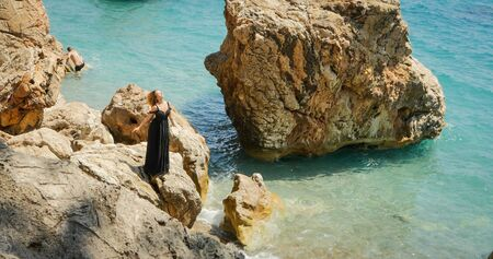 Young beautiful woman in long black dress standing on the rocks by the sea in windy weather