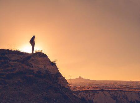 Silhouette of traveler looking at Uchisar, Cappadocia, Turkey. Sunset over beautiful sunset rocks of Cappadocia