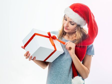 Young woman in Christmas Santa hat holding white gift box with red ribbon and looking at it over white background Stock Photo