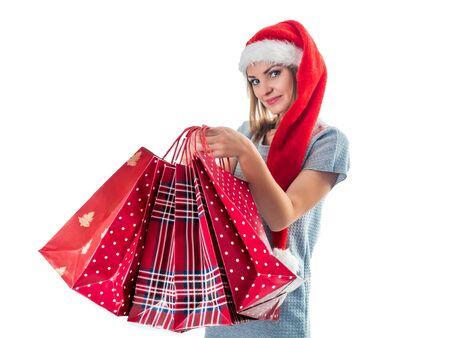 Ritratto di una donna felice con un lungo cappello rosso da Babbo Natale con le borse della spesa di Natale su sfondo bianco