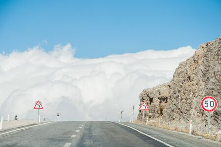 Empty road goes directly to the white fluffy clouds.