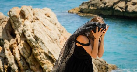 Young beautiful woman in black dress on the rocks by the sea in windy weather. Closing her face with black transparent scarf. Standard-Bild - 140456751