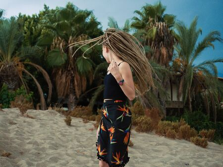 Portrait of fashionable full of life girl with dreadlocks over summer background with palms and sand. Summer youth vacation.