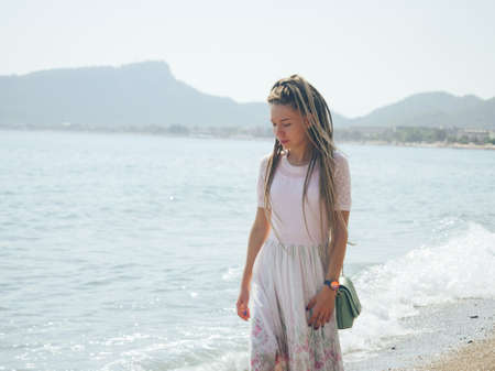 Dreadlocks fashionable girl walking alone near the sea