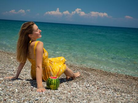 Young woman in yellow dress sitting on the pebble beach with watermelon cocktail. Summer vacation concept Standard-Bild