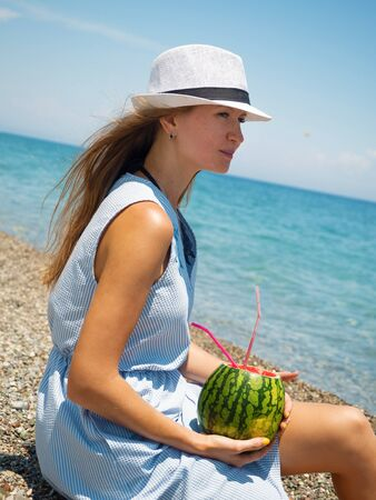 Young woman in hat sitting on the pebble beach with watermelon cocktail. Summer vacation concept