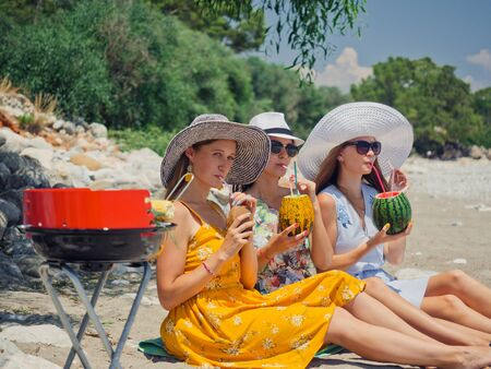 Three friends drinking fruit cocktails having picnic with grilled corn on the beach near the sea. Summer vacation concept