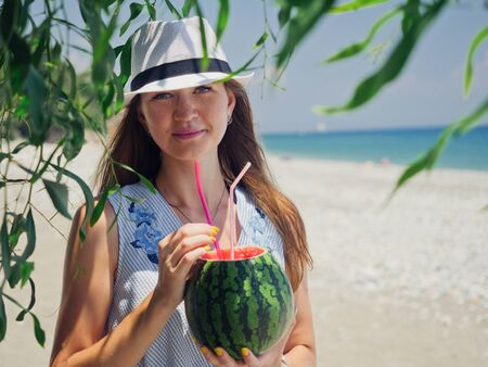 Portrait of happy smiling woman in hat holding watermelon cocktail on sea background