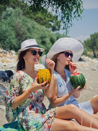 Two friends drinking fruit cocktails relaxing on the beach near the sea. Summer vacation concept