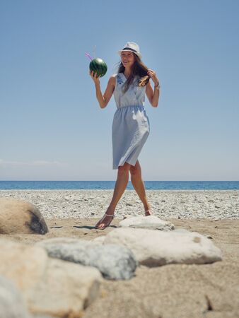 Happy smiling woman in hat holding watermelon cocktail on sea background