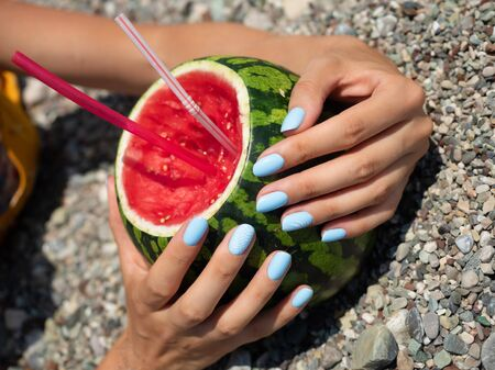 Blue manicured hands holding watermelon cocktail. Colorful summer days concept.