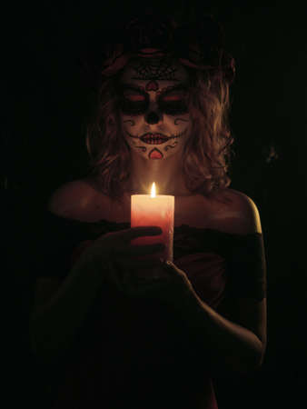 Santa muerte makeup young woman in pink dress holding burning candle on black background
