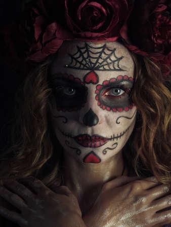 Studio portrait of Santa Muerte makeup woman standing on black background on Halloween eve