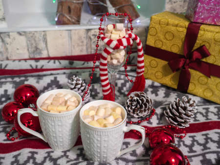 Hot chocolate with small marshmallows on the floor on Christmas presents and lights background