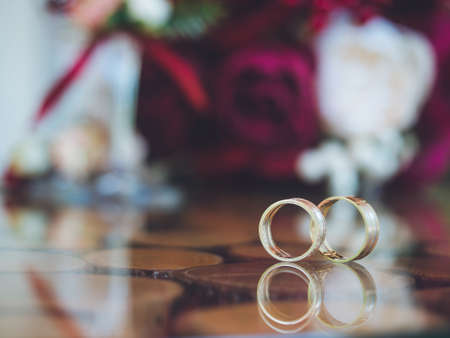 Closeup of wedding rings on the table of glass and wood. Bouquet in bokeh