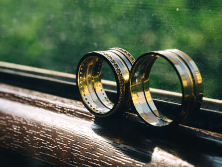 Closeup of golden wedding rings on the wooden window.