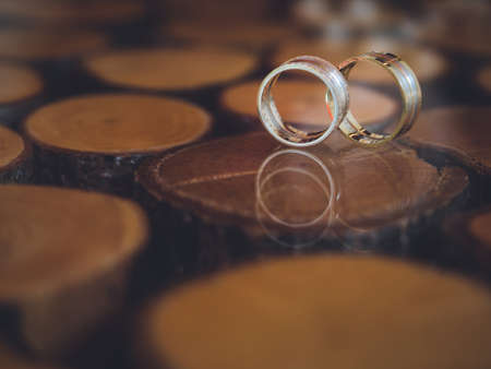Closeup of wedding rings on unusual design table of glass and wood. 写真素材