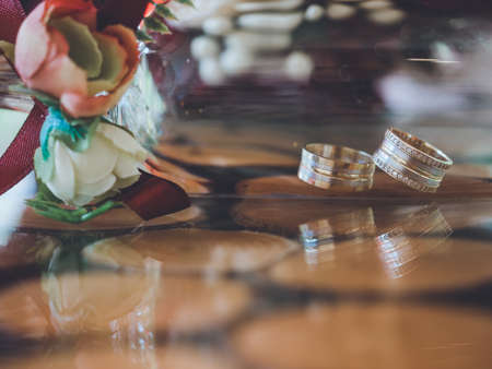 Closeup of golden wedding rings in decorative champagne glass on reflective design table