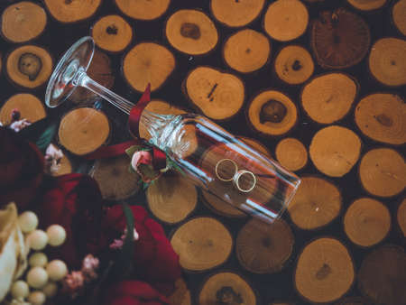 Closeup of golden wedding rings in decorative champagne glass on table of glass and wood