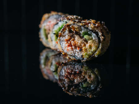 Closeup of tempura rolls with eel and snow crab on reflective dark table.