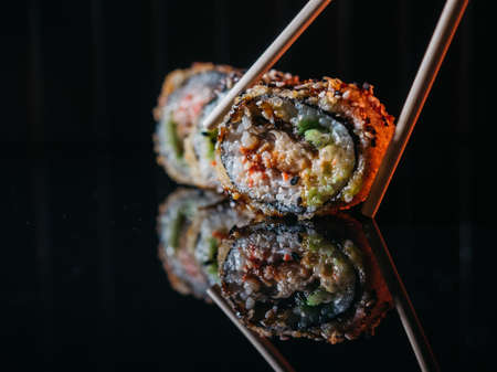 Closeup of tempura rolls with eel and snow crab taking with chopsticks from reflective dark table.