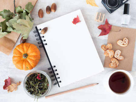 Top view of office workspace with open empty white spiral notepad, autumn leaves, decorative pumpkins and cup of tea with biscuits Stok Fotoğraf