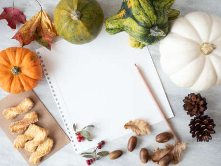 White empty paper with red pencil, autumn leaves, pumpkins, acorns, cones and cookies on the table Stok Fotoğraf