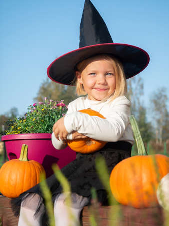 3 years old girl in witch costume sitting with pumpkins on wooden terrace.