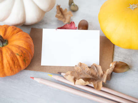 Empty white business card on retro style envelope, some colorful pencils and autumn oak leaves, acorns and decorative pumpkins on the table Stok Fotoğraf