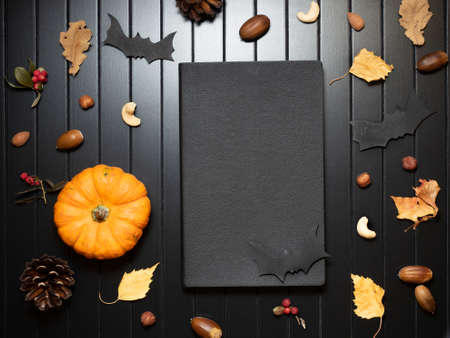 Top view on closed black notepad with decorative pumpkin and autumn leaves, berries, acorns, cones. Traditional Halloween decor.
