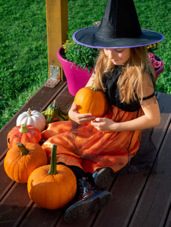 6-7 years old adorable girl in witch costume holding pumpkin sitting on wooden terrace Stok Fotoğraf