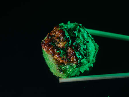Baked sushi roll with green tobiko caviar held with chopsticks on black background