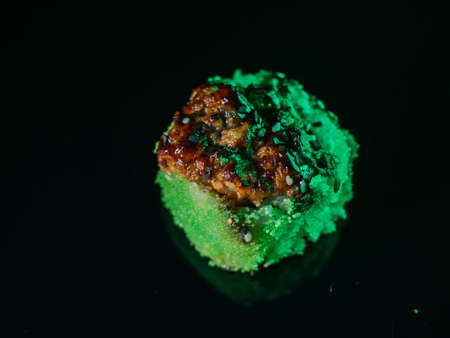 Baked sushi roll with green tobiko caviar on black reflective background