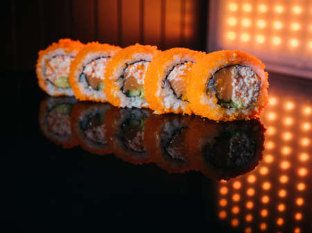 Sushi rolls with orange tobiko caviar, salmon and avocado snow crab lighted up with red led lights on reflective background Stok Fotoğraf