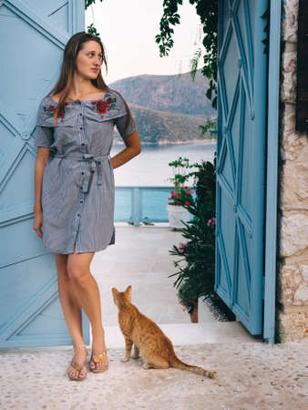 Young woman with cat standing near blue open door with beautiful sea resort view.