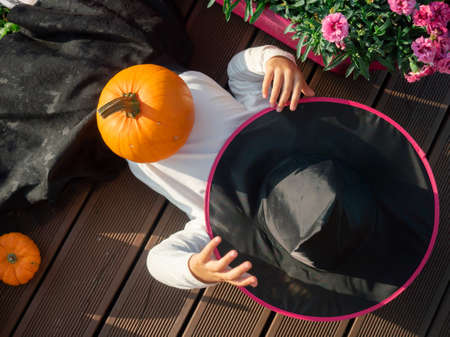 Top view of 3 years old girl in witch costume lying with pumpkin on wooden terrace