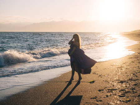 Young beautiful woman 7 month pregnant in violet dress enjoying Mediterranean sea in sunset time