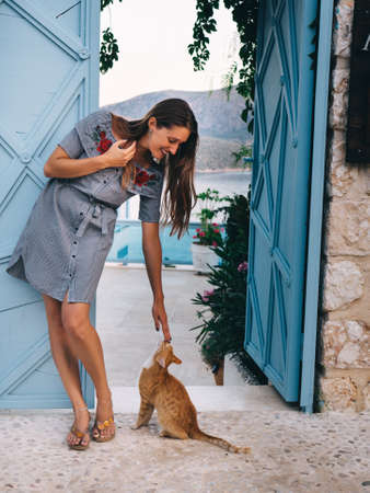 Young woman stroking red cat near blue open door with beautiful sea resort view.