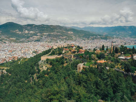 Wide view to Alanya city with Castle ruins in front view. Mountains and clouds on background